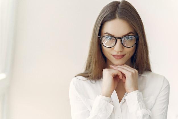 Donna di affari in una camicia bianca che si siede nell'ufficio