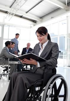 Donna di affari in una sedia a rotelle che legge un rapporto