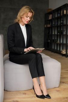 Donna di affari in vestito facendo uso della compressa