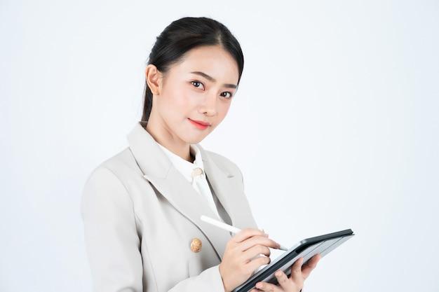 Donna di affari in vestito grigio facendo uso della compressa e della penna per registrare i verbali della riunione e del lavoro.
