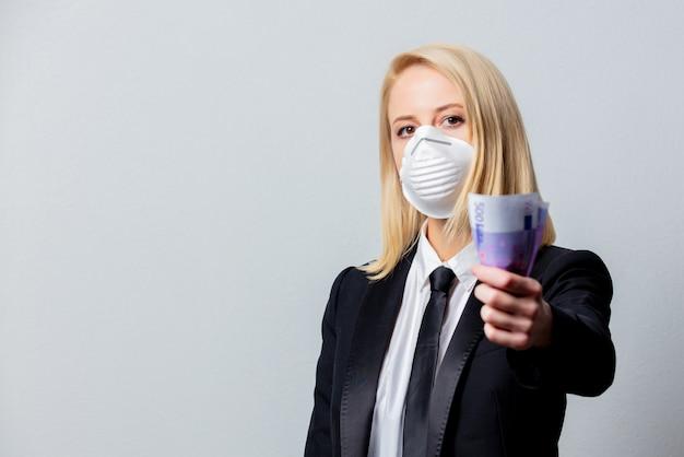 Donna di affari in vestito nero e maschera con soldi
