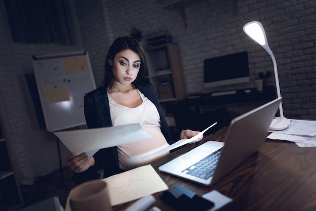 Donna di affari incinta stanca che lavora nell'ufficio