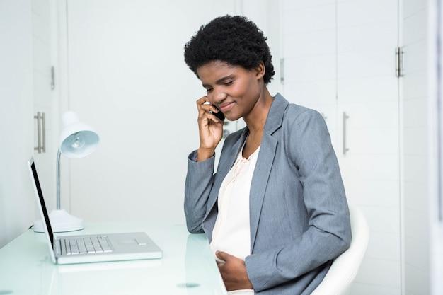Donna di affari incinta sul telefono nell'ufficio