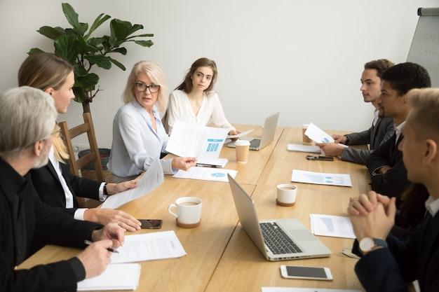 Donna di affari invecchiata seria che discute rapporto finanziario corporativo alla riunione della squadra