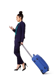 Donna di affari itinerante che cammina con la borsa e il telefono cellulare