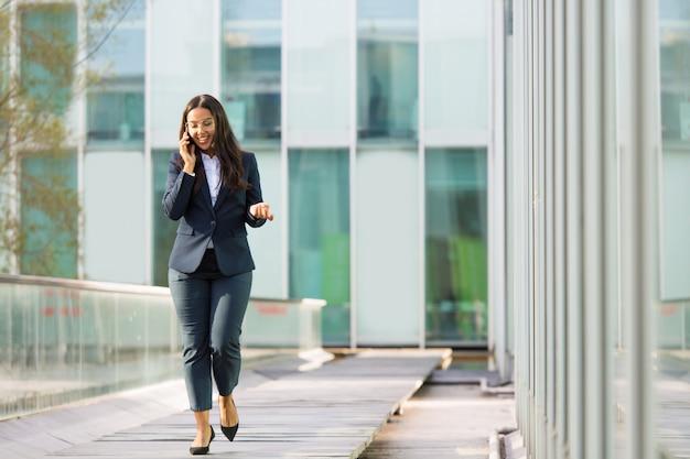 Donna di affari latina allegra felice che parla sul telefono