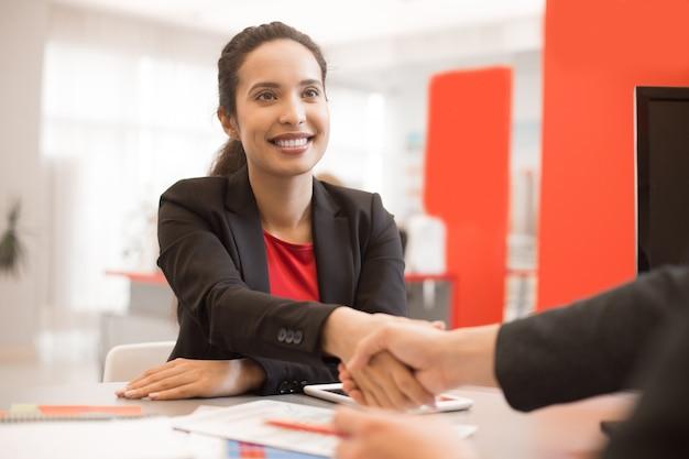 Donna di affari latina che stringe le mani con il partner