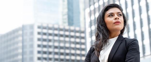 Donna di affari latina potente nella priorità bassa della bandiera dell'edificio per uffici della città