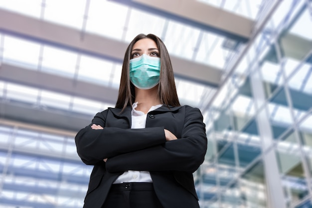 Donna di affari mascherata davanti al suo ufficio, pandemia di coronavirus e concetto del lavoro