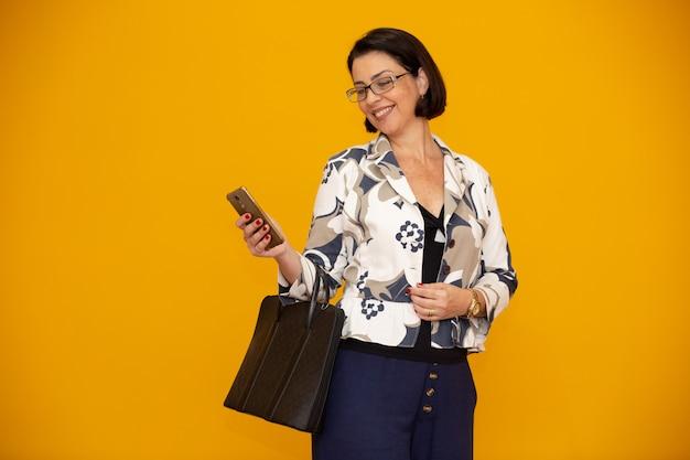 Donna di affari matura attraente che lavora con il suo telefono cellulare