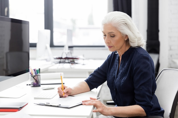 Donna di affari maturi che fa le note su un pezzo di carta