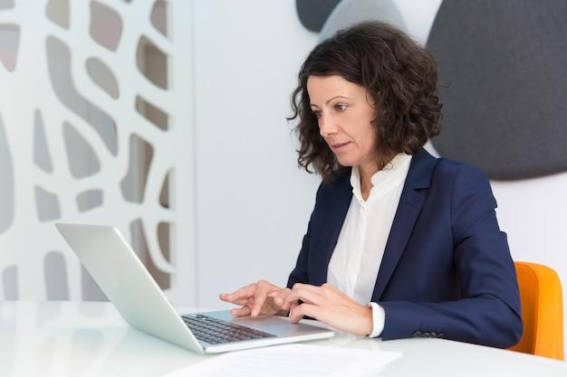 Donna di affari messa a fuoco che lavora al computer