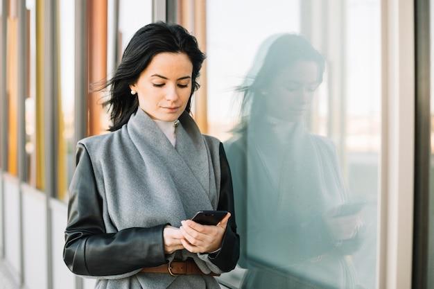 Donna di affari moderna che utilizza smartphone all'aperto