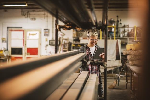 Donna di affari motivata professionale concentrata laboriosa che tiene una compressa accanto allo scaffale con tubi di metallo nell'officina del tessuto