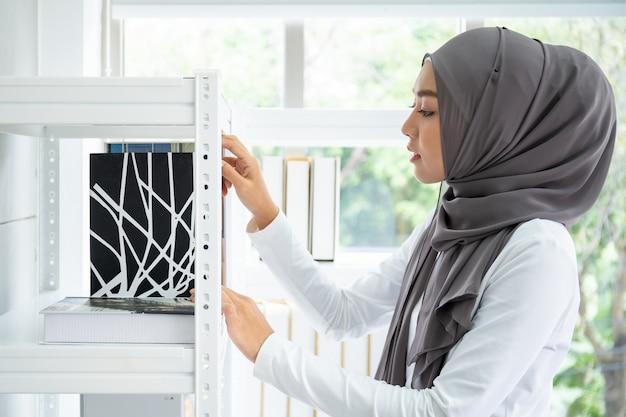 Donna di affari musulmana asiatica che sceglie i libri sullo scaffale di libro nel suo ufficio, studentessa musulmana.