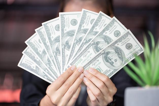Donna di affari nel suo ventilatore della banconota in dollari della tenuta dell'ufficio