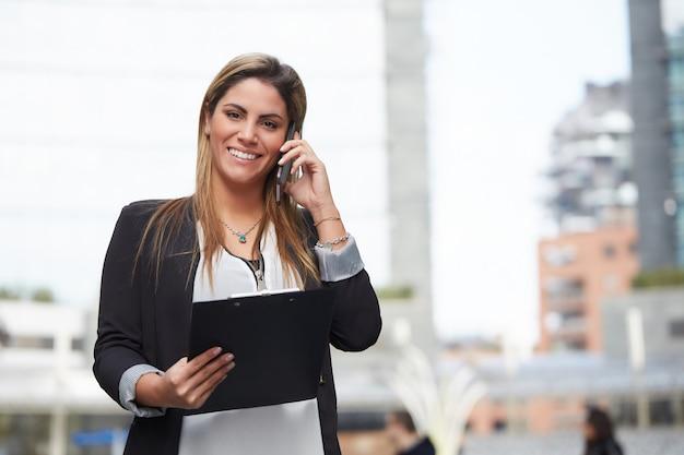 Donna di affari nell'ambiente urbano che parla con cellulare