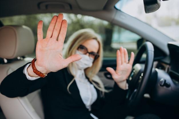 Donna di affari nella maschera di protezione che si siede dentro un'automobile facendo uso dell'antisettico