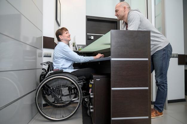 Donna di affari nella vista lunga dell'uomo e della sedia a rotelle