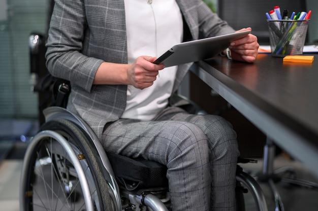 Donna di affari nella vista media della sedia a rotelle