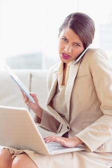 Donna di affari occupata e sollecitata che si siede sul multi incarico del sofà
