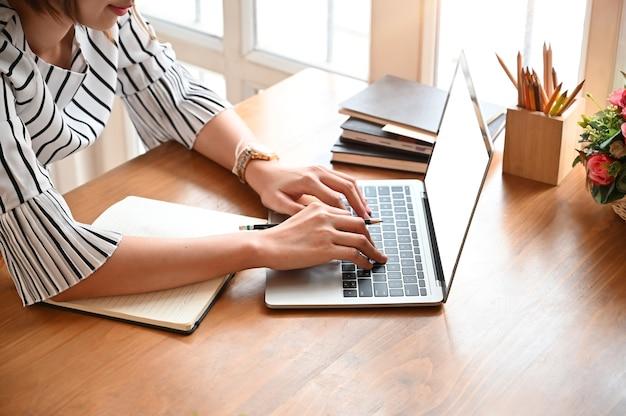 Donna di affari potata della foto del colpo facendo uso del computer portatile del modello