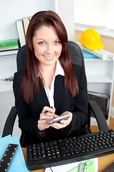 Donna di affari radiante che per mezzo del suo calcolatore che esamina la macchina fotografica