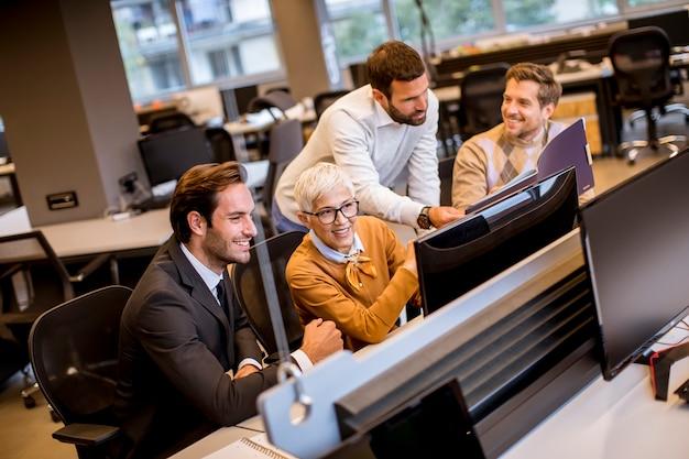 Donna di affari senior che lavora insieme ai giovani uomini d'affari in ufficio moderno