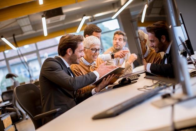 Donna di affari senior che lavora insieme ai giovani uomini d'affari in ufficio