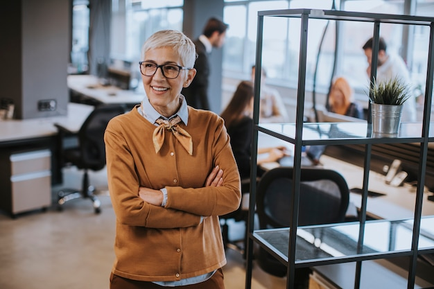 Donna di affari senior che sta nell'ufficio