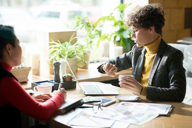 Donna di affari seria che controlla tempo alla riunione nella caffetteria