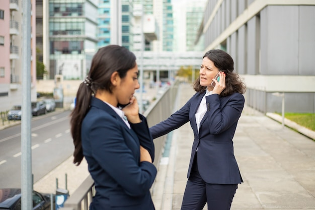Donna di affari seria che parla dallo smartphone