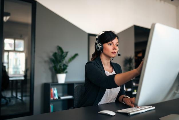 Donna di affari seria con la cuffia avricolare che risolve i problemi mentre lavorando al computer in ufficio moderno.
