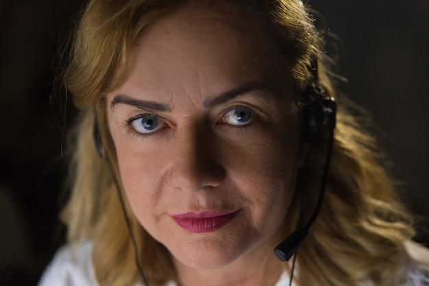 Donna di affari seria nello sguardo della cuffia avricolare