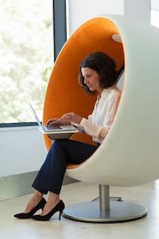Donna di affari sicura che lavora al computer
