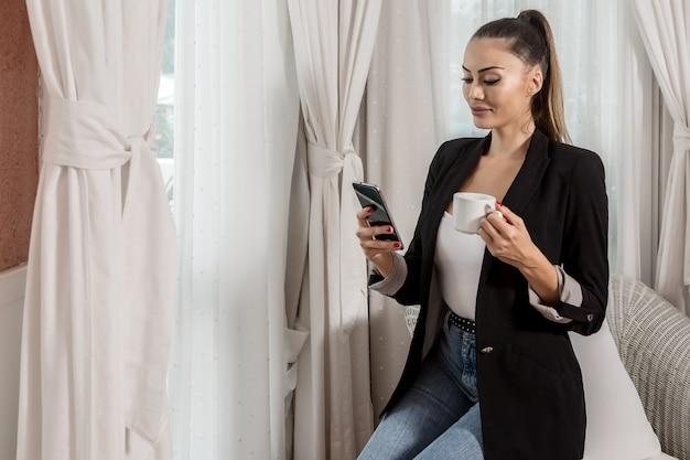 Donna di affari sicura che per mezzo dello smartphone e bevendo caffè