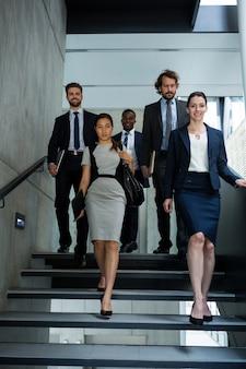 Donna di affari sicura con i colleghi che scendono le scale