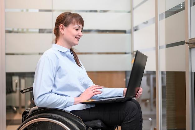 Donna di affari sicura nel funzionamento della sedia a rotelle