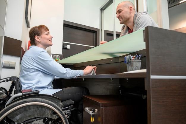 Donna di affari sicura nella conversazione della sedia a rotelle con un cliente