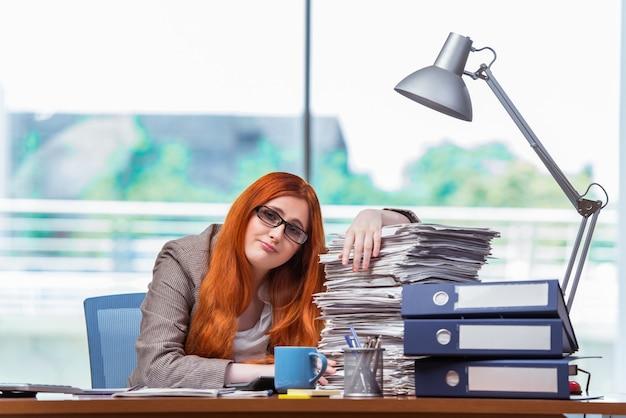 Donna di affari sollecitata con la pila di documenti
