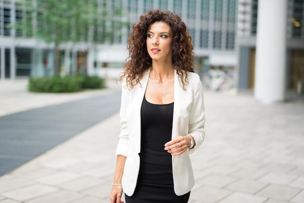 Donna di affari sorridente che cammina in una città moderna