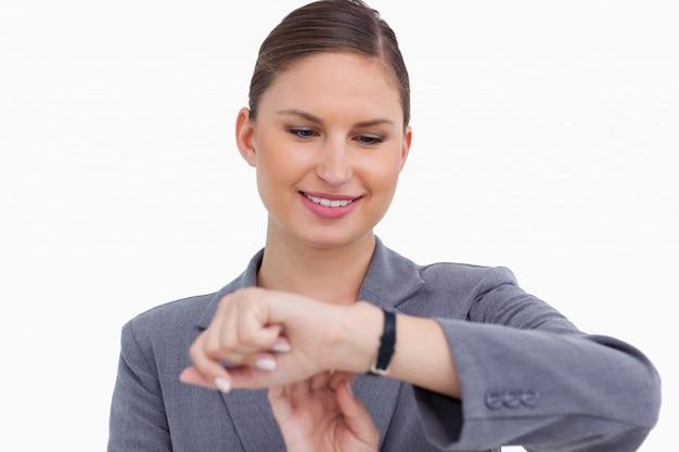 Donna di affari sorridente che controlla la sua vigilanza
