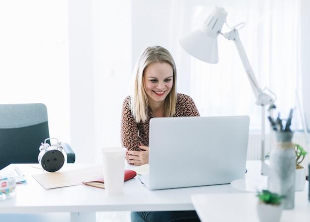 Donna di affari sorridente che esamina computer portatile