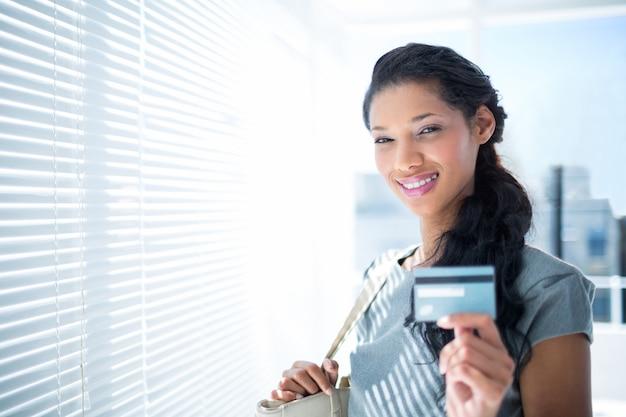 Donna di affari sorridente che esamina macchina fotografica con la carta di credito