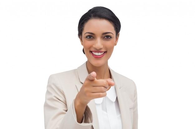 Donna di affari sorridente che indica alla macchina fotografica