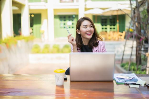 Donna di affari sorridente che lavora nell'ufficio con i documenti