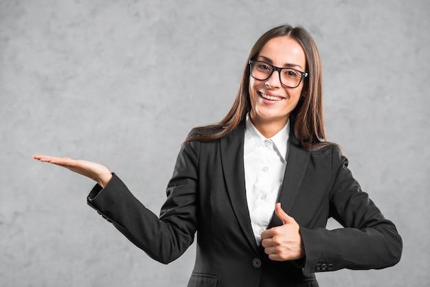 Donna di affari sorridente che mostra pollice sul segno che presenta contro il fondo grigio