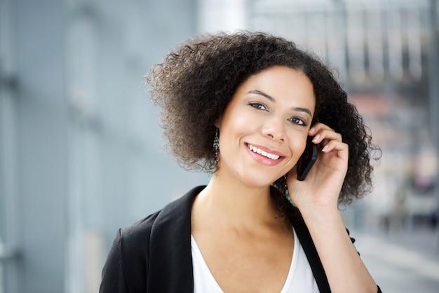 Donna di affari sorridente che parla sul telefono cellulare