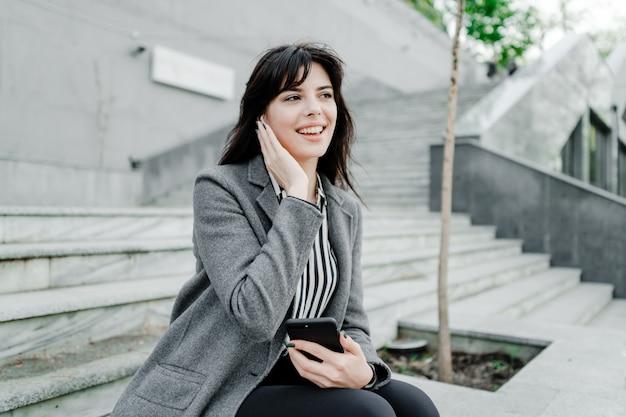 Donna di affari sorridente che parla sul telefono tramite i tappi per le orecchie senza fili