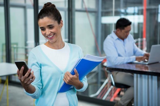 Donna di affari sorridente che per mezzo del telefono cellulare mentre stando con i documenti